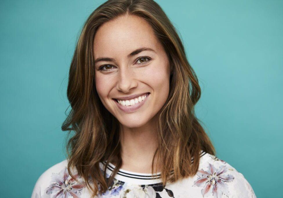 Confident brunette smiling to camera, studio shot